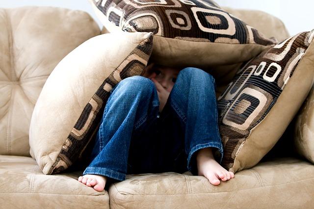 dítě schované v polštářích