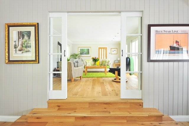 Schody a dveře do obývacího pokoje, kde je sedací souprava, křesla, stůl a obrazy