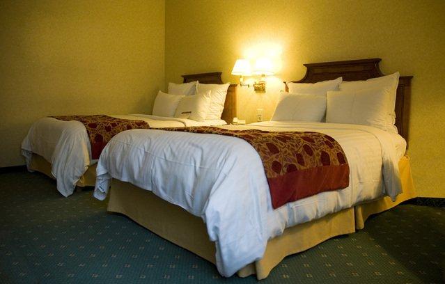 postele u žluté zdi s rozsvícenou lampičkou