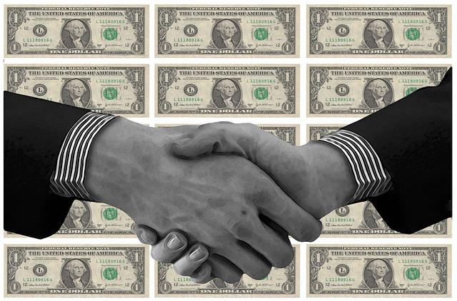 Potřesení rukou dvou podnikatelů a v pozadí jsou bankovky