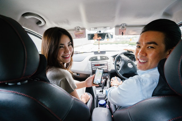 dva lidi sedící v autě
