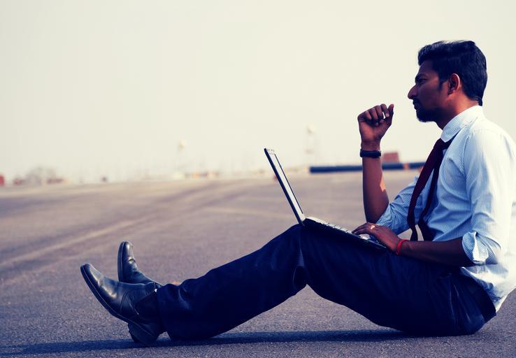 člověk v modré košili s kravatou sedí na silnici a má na klíně laptop