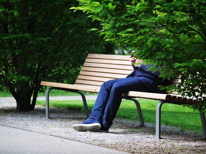 park, lavička, na ní sedí muž v modrém obleku s mobilem v ruce, tvář a půl těla má za stromem